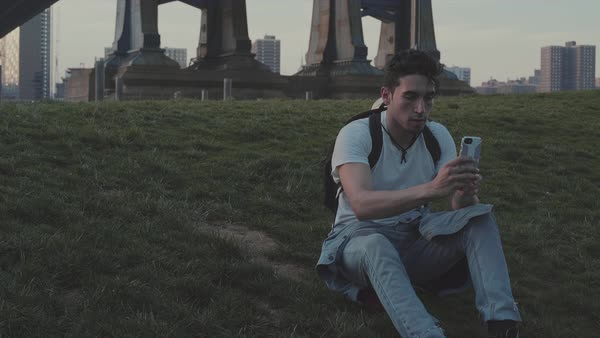 Hand-held shot of a young man taking a selfie outside on a grassy hill Royalty-free stock video