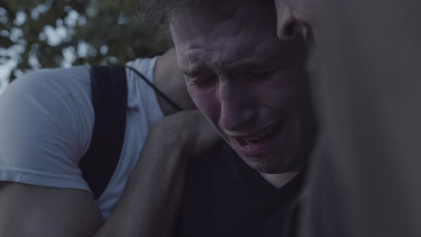 Hand-held shot of a young man crying and being comforted by his friends outside Royalty-free stock video