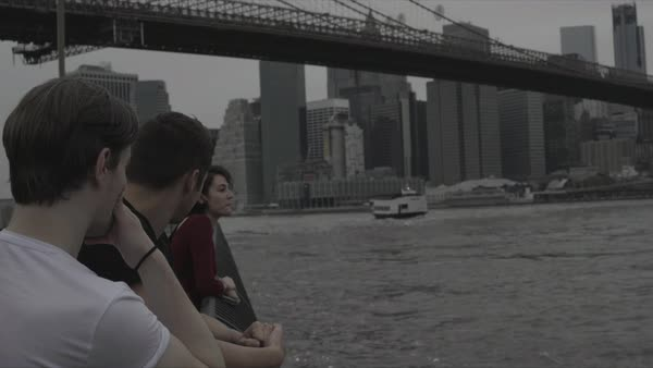 Hand-held shot of three people looking at East River Royalty-free stock video
