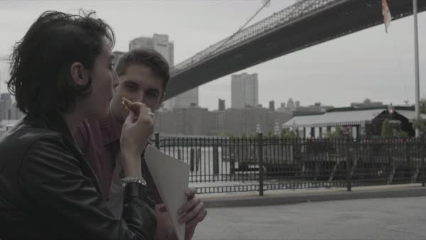 Hand-held shot of a couple eating on a bench in New York Royalty-free stock video