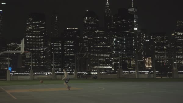 Hand-held shot of a man playing basketball at night outdoors Royalty-free stock video