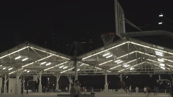 Hand-held shot of people playing basketball at night outdoors Royalty-free stock video
