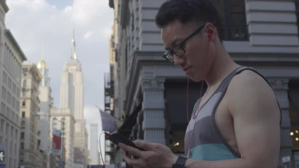Gimbal shot of a man using a cell phone on a street in New York City Royalty-free stock video