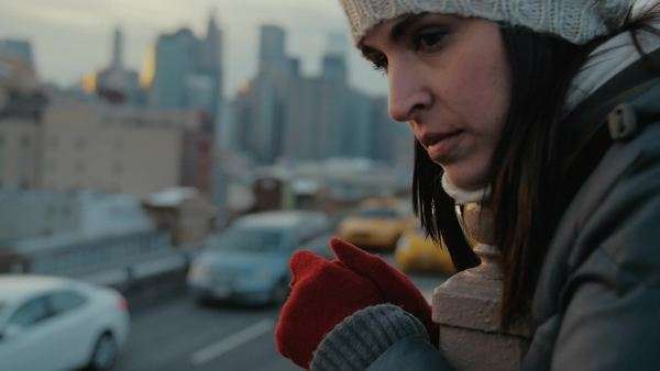 Sad attractive young woman wearing gloves and hat looking down.  Manhattan in the background. Royalty-free stock video