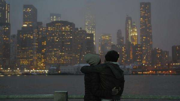 Wide cinematic shot of young couple and Manhattan skyline at night in Wintertime Royalty-free stock video