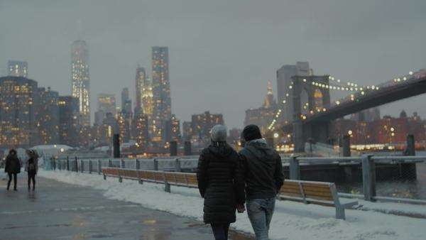 Young couple walking along Brooklyn waterfront in winter with Manhattan skyline in background Royalty-free stock video
