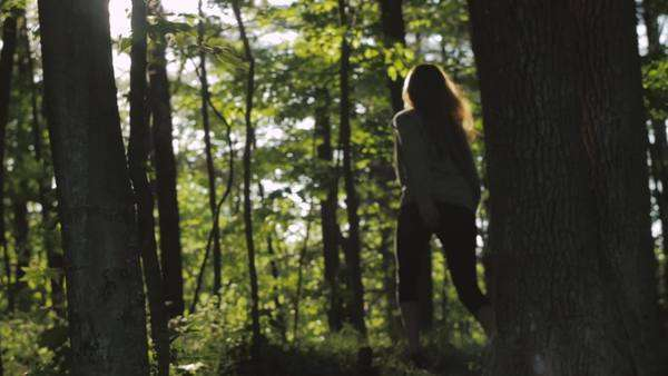 Wide shot of a woman walking in a forest Royalty-free stock video