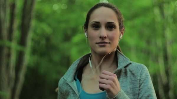 Close-up of a young woman jogging in a forest Royalty-free stock video