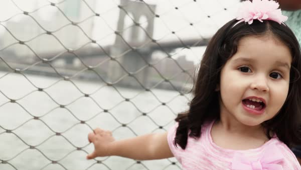 Close-up shot of little girl standing beside the Brooklyn Bridge Royalty-free stock video