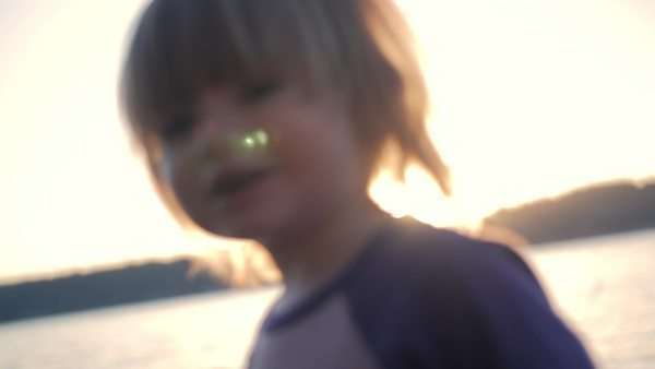Cute little girl plays in the water on the beach during golden hour. Royalty-free stock video