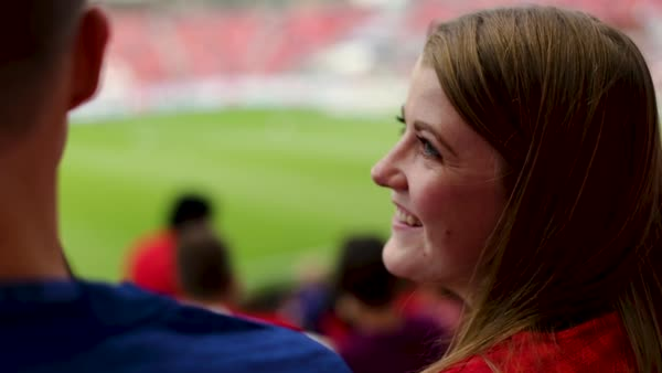 Close-up of young woman talking and laughing with man at professional soccer game Royalty-free stock video