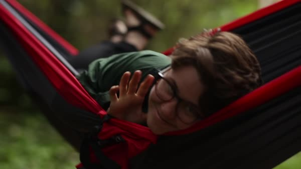 Portrait Of Happy Camper Relaxing In Hammock, Waves Hello To Camera, Smiles  Royalty-free stock video