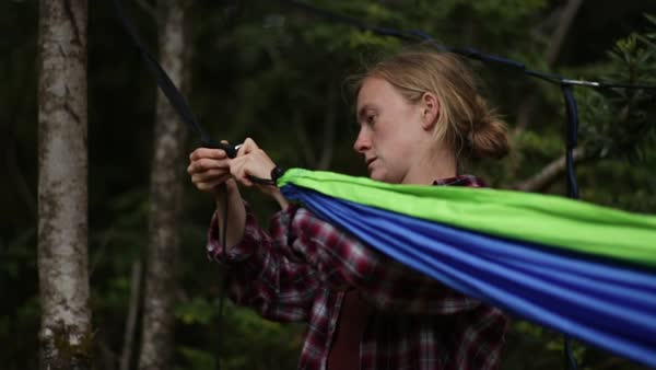 Young Woman Sets Up A Hammock For Camping In A Forest (Slow Motion) Royalty-free stock video