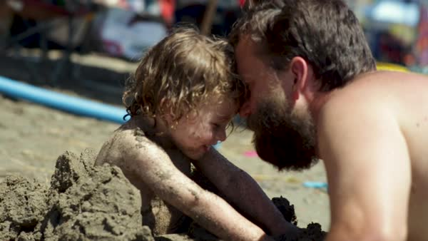 Father plays with his little boy at beach, his son is buried in sand, cute moment (slow motion) Royalty-free stock video