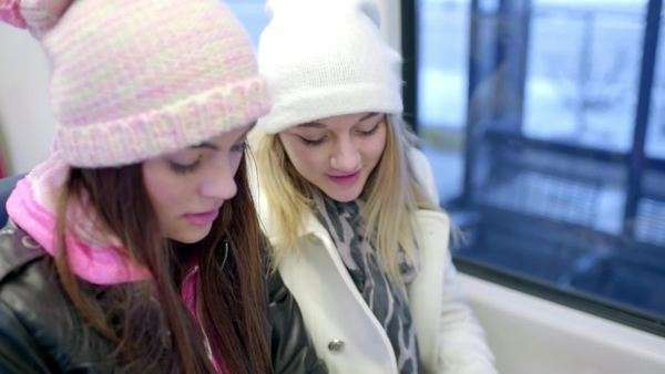 Two young women look at train schedule to figure out their route Royalty-free stock video
