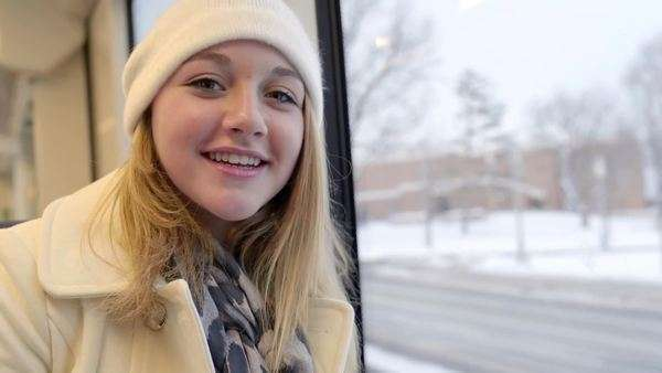 Closeup of happy teenager traveling on a train in winter, she smiles wide Royalty-free stock video