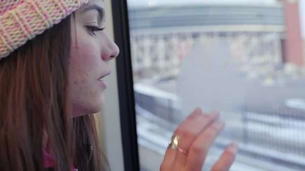 Teen rides the train, she blows on cold window to fog it up, then she draws a peace sign (slow motion) Royalty-free stock video