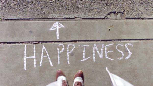 "Birds eye view of woman's feet dancing on the sidewalk next to chalk letters that spell out, ""happiness"" Royalty-free stock video"