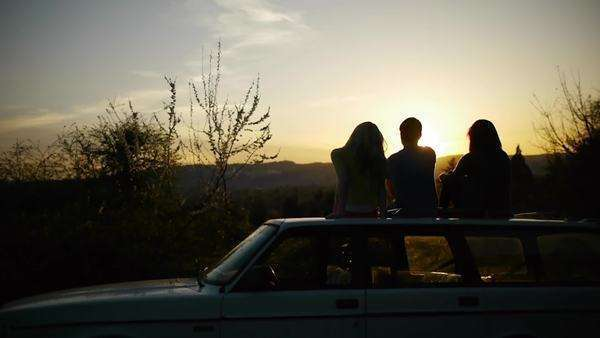 Teens watching sunset on top of car Royalty-free stock video