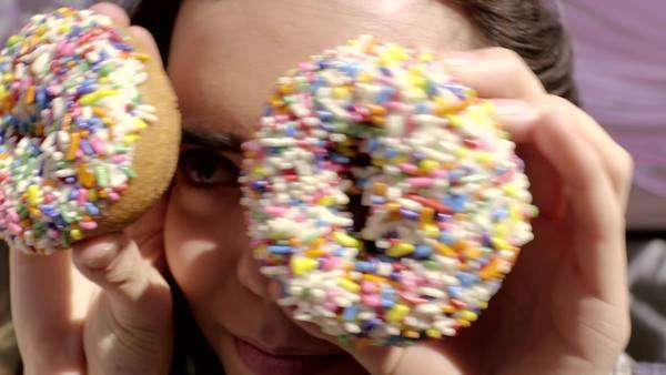 Close-up of teen covers her eyes with donuts and makes them dance around Royalty-free stock video