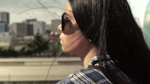 Close-up of young woman enjoying the view of a city from a bridge. slow motion Royalty-free stock video
