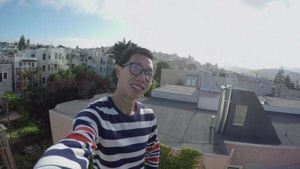 Chinese man takes a selfie on a rooftop with beautiful San Francisco neighborhood in the background Royalty-free stock video