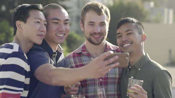 Group of friends celebrate on a rooftop in San Francisco, they take photos together Royalty-free stock video