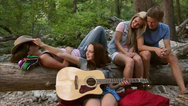 2 girls lay on a log their friend plays guitar and they laugh
