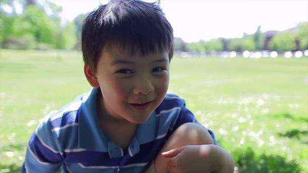 Little boy sitting in a field, looks at the camera and makes funny faces (slow motion) Royalty-free stock video