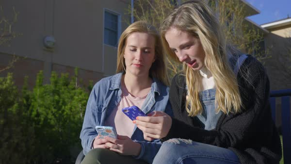 Friends sit on bench they chat and use smartphones Royalty-free stock video