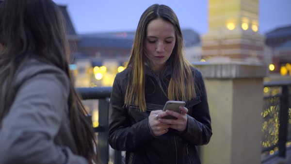 Teens hang out on rooftop, girl tries to take her friend's phone away, so she will stop texting Royalty-free stock video