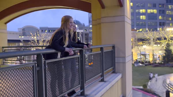 Girls hang out on balcony, one waves to people in distance, their friend joins them and they all enjoy view Royalty-free stock video