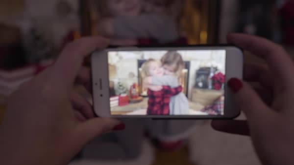 Mom takes video of her two children hugging by cozy fireplace decorated for Christmas Royalty-free stock video