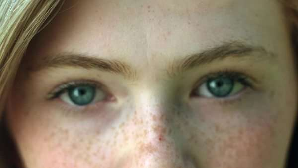 A closeup of a young woman's eyes, she stares into camera, then her eyes brighten as she smiles Royalty-free stock video