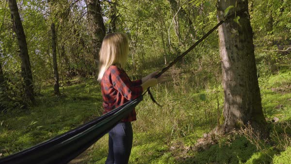 Young woman secures hammock to tree, then attempts to sit in hammock, she falls over instead, she gets up and laughs Royalty-free stock video