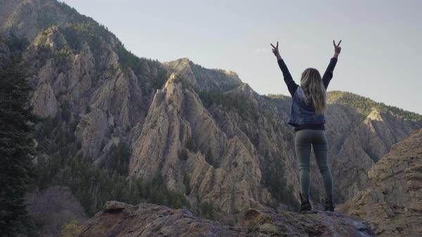 Adventurous Young Woman Stands On Top Of Peak In Utah Mountains And Holds Up Peace Signs Royalty-free stock video