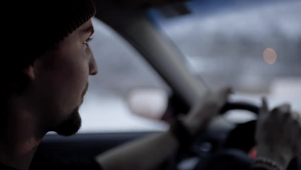 Slow motion close-up of young man's face as he drives on a snowy winter night Royalty-free stock video
