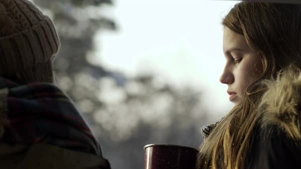 Two teen girls relax and chat, brunette drinks hot cocoa, outdoors on a winter day Royalty-free stock video