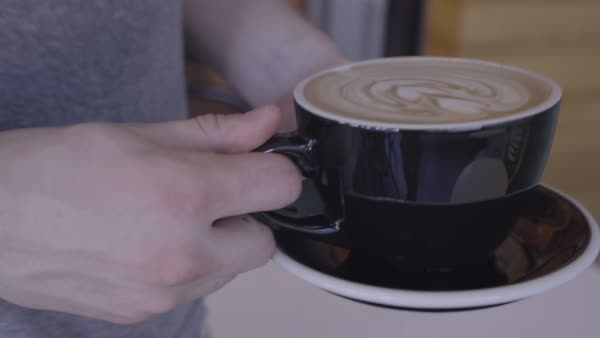 Man Brings His Beautiful Girlfriend Her Cappuccino, With A Heart On The Top, She Smiles Royalty-free stock video