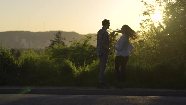Man Twirls His Girlfriend, Then Pulls Her In Close For Romantic Kiss At Sunset, City In Background, Slow Motion  Royalty-free stock video
