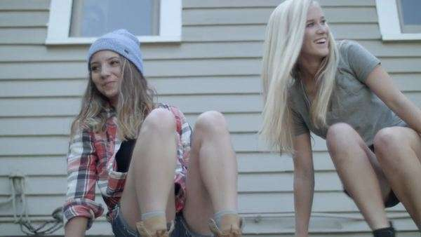 2 excited teen girls climb up onto roof for fun Royalty-free stock video