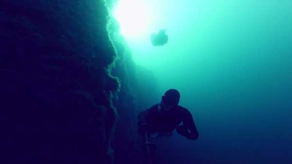 Deep freedivers exploring an underwater cliff into a quarry Royalty-free stock video