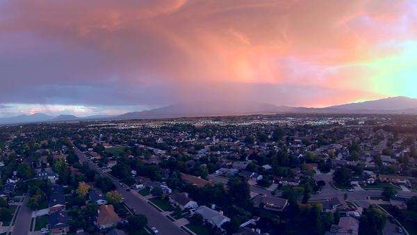 Storm clouds coming towards urban neighborhood with beautiful clouds from sunset and lightning strikes the ground. Royalty-free stock video