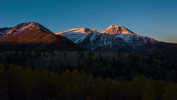 sun catch these snowy mountain peaks as the sunrise creates an orange glow that makes its way down the mountain.  The fall aspen tress continue to light up as the sun continues to rise. Royalty-free stock video