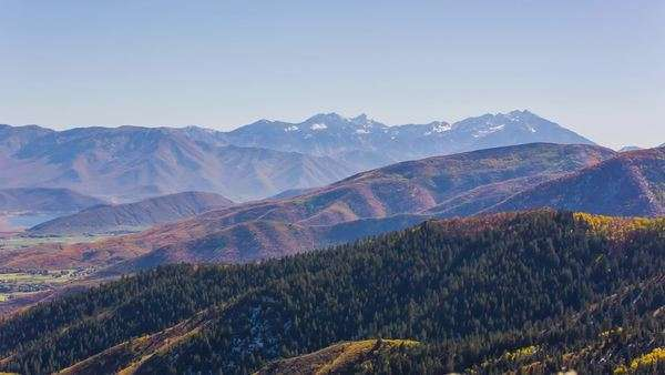 Rocky mountains pan across to show small mountain town in the valley below Royalty-free stock video