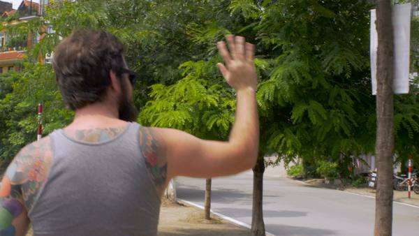 Steadicam of a bearded young hipster man wearing a grey tank top t shirt with colorful tattoos who is waiving to people on the street as he walks along a lake outside on a warm summer day. Royalty-free stock video