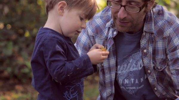 Little blond boy holding and looking at a Fall leaf with his 30 something father outside in green yard with soft focus and slow motion Royalty-free stock video