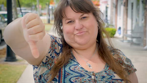 Disappointed frustrated full figured plus size woman gives the thumbs down shaking her head no outside on urban city sidewalk Royalty-free stock video