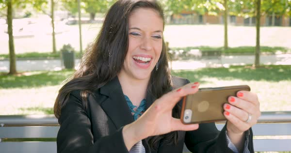 Pretty traveling woman in business suit using smart phone for video conferencing call waving hello outside on park bench in public dolly shot Royalty-free stock video