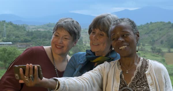 Three lively senior women in 60s on vacation taking selfies with smart phone and looking at photos outside their vacation rental Royalty-free stock video